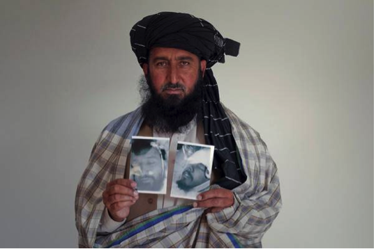 Karim Khan holding up pictures of Asif and Zahinullah (deceased)